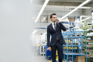 Businessman on cell phone in a factory - DIGF05759