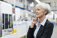 Portrait of senior businesswoman in a factory looking around - DIGF05762
