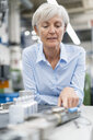Portrait of senior businesswoman in a factory looking at workpiece - DIGF05768