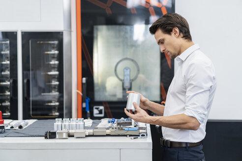 Businessman examining workpiece in a factory - DIGF05771