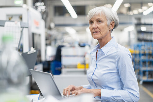 Senior businesswoman using laptop in a factory - DIGF05777