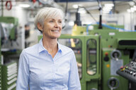 Portrait of smiling senior businesswoman in a factory looking around - DIGF05786