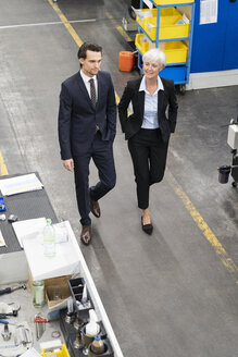 Businessman and senior businesswoman walking in a factory - DIGF05816