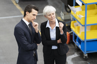 Businessman and senior businesswoman talking in a factory - DIGF05819