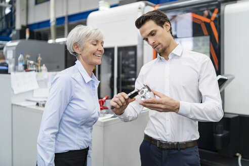 Businessman and senior businesswoman measuring workpiece in a factory - DIGF05822