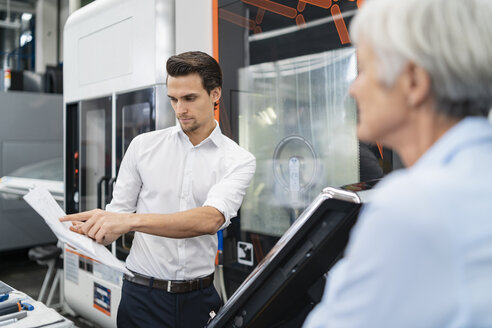 Businessman and senior businesswoman with manual at a machine in a factory - DIGF05831