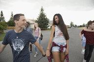 Teenage friends walking on neighborhood street - HEROF21829