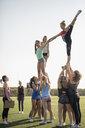 Teenage girl high school cheerleading team practicing lift on football field - HEROF21859