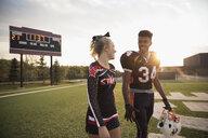 Teenage high school cheerleader and football player walking n football field - HEROF21874