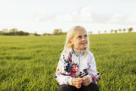 Thoughtful girl looking away while sitting on grassy field - ASTF02821