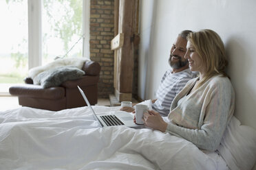 Couple drinking coffee and using laptop in bed - HEROF21904