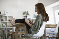 Comfortable barefoot teenage girl texting with cell phone with feet up on dining table - HEROF21994