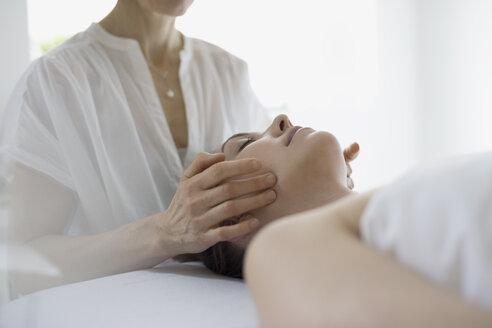 Serene woman receiving face massage on spa massage table - HEROF22045