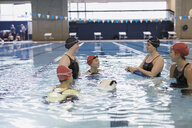 Young women swimmers talking in swimming pool - HEROF22102