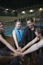 Smiling teenage girl swimmers connecting hands in huddle at swimming pool - HEROF22114