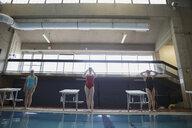 Young women swimmers preparing at edge of swimming pool - HEROF22123