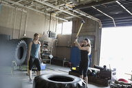 Strong woman hitting large tire with sledgehammer in crossfit training at gym - HEROF22138