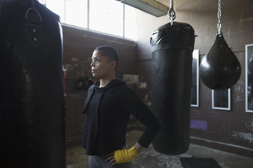 Serious female boxer looking away at punching bags in gritty gym - HEROF22171