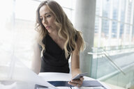 Serious businesswoman reading paperwork, using cell phone in office - HEROF22177