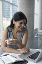 Smiling businesswoman drinking coffee and working at laptop - HEROF22180