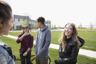Smiling college students talking, hanging out on college campus - HEROF22249