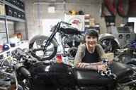 Portrait confident female motorcycle mechanic with tattoos in auto repair shop - HEROF22300