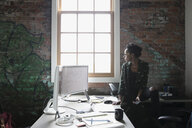Pensive creative businesswoman looking out window in office - HEROF22327
