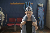 Portrait serious girl swimmer with towel around neck in locker room - HEROF22336