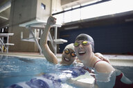 Portrait smiling female swimmers cheering and celebrating in swimming pool - HEROF22351