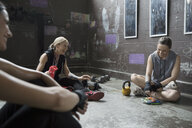Portrait confident women resting, eating snack post workout at gritty gym - HEROF22372