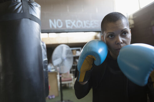 Portrait serious, tough female boxer in boxing gloves in fighting stance in gym - HEROF22381