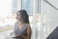Pensive businesswoman with coffee looking out office window - HEROF22408