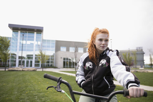 Portrait female college student with red hair riding bicycle on lawn on college campus - HEROF22453