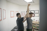 Male physiotherapist checking shoulder and arm of client in office - HEROF22459