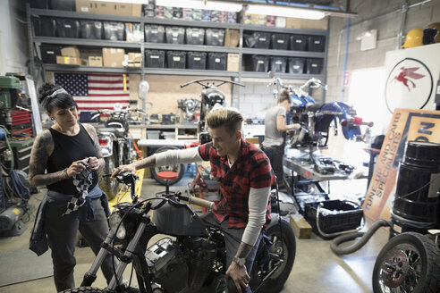Motorcycle mechanics talking, fixing motorcycle in auto repair shop - HEROF22573