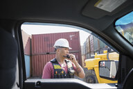 Male worker using walkie-talkie outside truck in industrial container yard - HEROF22582