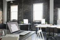 Laptop on desk in empty loft creative office - HEROF22585