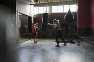 Mother boxer teaching daughter boxing at gym - HEROF22603