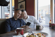 Male gay couple using cell phone in diner booth - HEROF22618