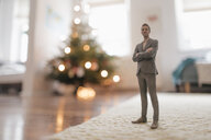 Businessman figurine standing next to a Christmas tree at home - FLAF00151