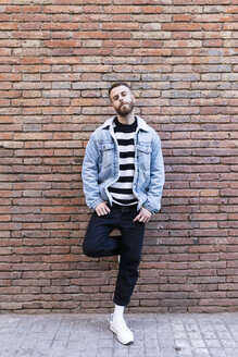 Portrait of a cool man standing at a brick wall - JRFF02618