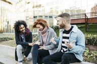 Three happy friends sitting in the city talking - JRFF02624