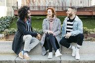 Three happy friends sitting in the city talking - JRFF02627
