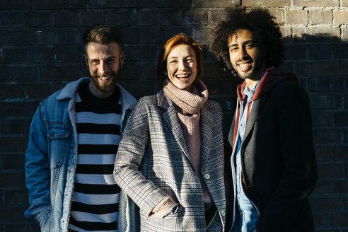 Portrait of three happy friends in shadow at a brick wall - JRFF02636