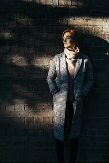 Young woman standing at a brick wall in shadow looking sideways - JRFF02639