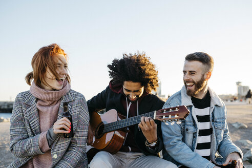 Three happy friends with guitar sitting outdoors at sunset - JRFF02654
