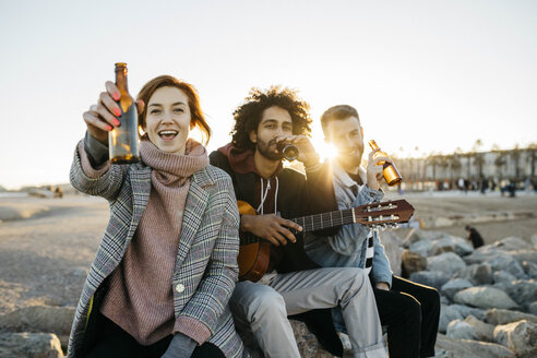 Three happy friends with guitar toasting beer bottles at sunset - JRFF02657