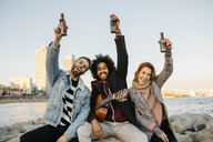 Portrait of three happy friends with guitar raising beer bottles at the coast sunset - JRFF02660
