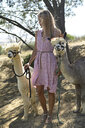 Blond woman with two leashed alpacas - ECPF00493