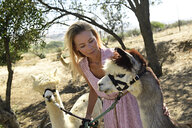 Portrait of blond woman with two leashed alpacas - ECPF00496